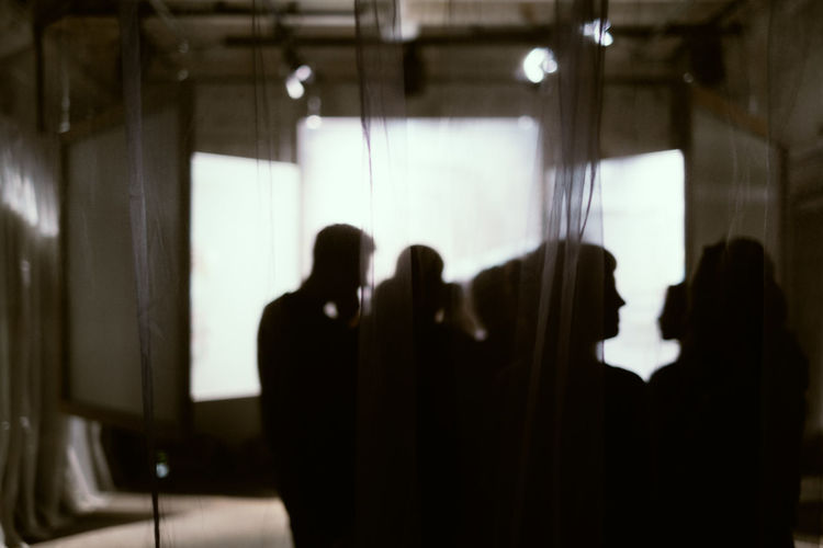 Silhouette people standing against illuminated lighting equipment in studio