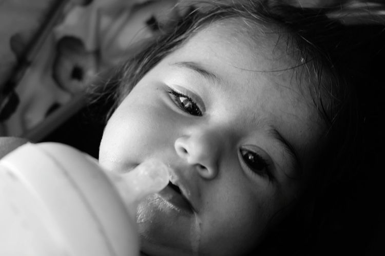 High angle portrait of cute girl with baby bottle