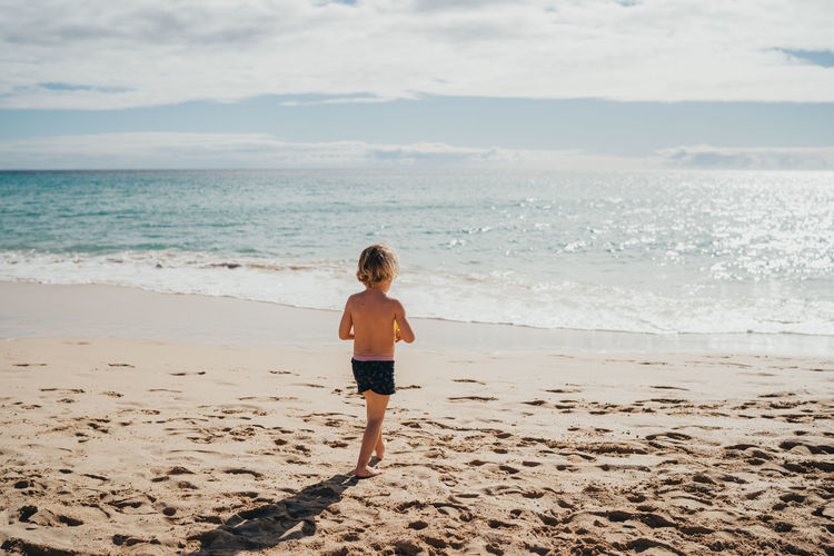Rear view of boy standing on beach