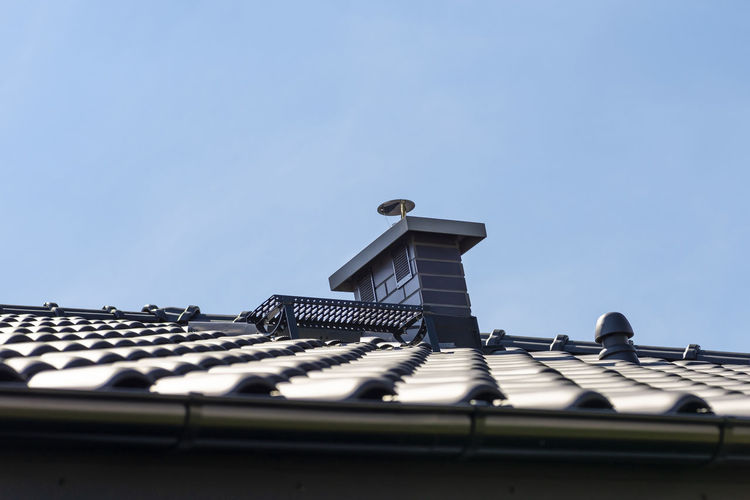 The roof of a single-family house covered with a new ceramic tile in anthracite, system chimney