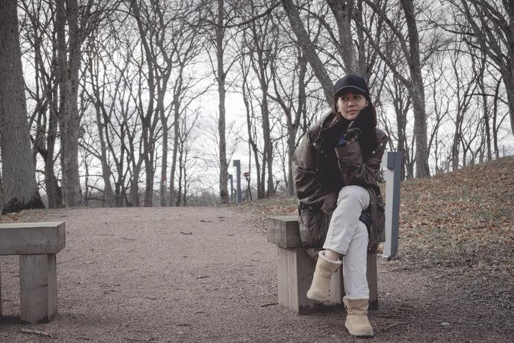 Full length portrait of woman sitting in park