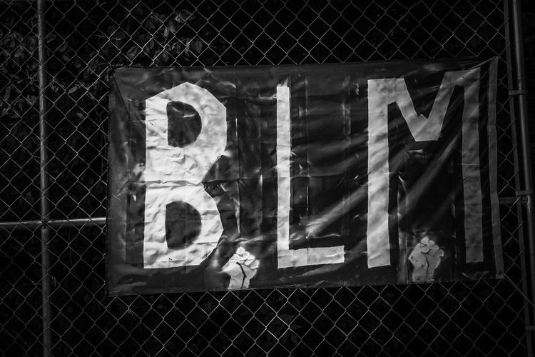 Close-up of text on chainlink fence at night