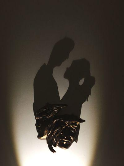 Silhouette people holding illuminated light against dark background