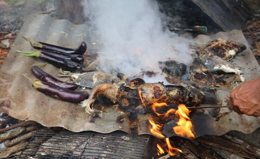 High angle view of person preparing food over fire