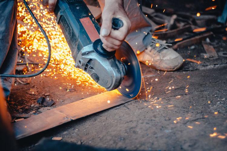 Close-up of man grinding metal