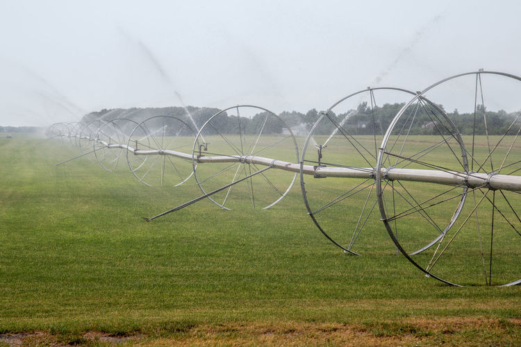 Agricultural sprinkler spraying on grassy field at farm against sky
