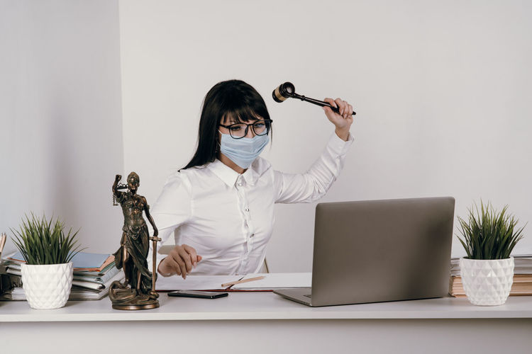 Young frustrated lawyer wearing mask hitting laptop by hammer at office