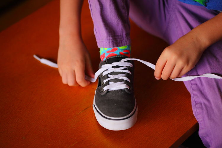 Midsection of girl tying shoelace at home