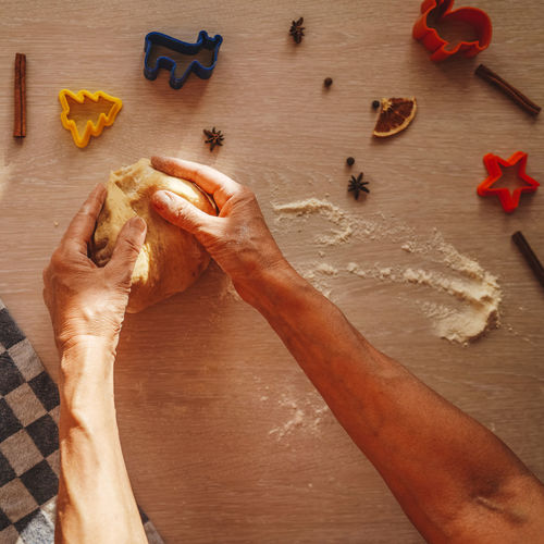Cropped hands of woman kneading dough on table