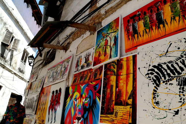 Multi Colored Art And Craft Creativity Graffiti Architecture No People Built Structure Wall - Building Feature Building Exterior Human Representation Low Angle View Hanging Zanzibar Zanzibar_Tanzania Zanzibarisland Zanzibar Africa Sansibar Africa Stonetown Stonetownzanzibar Holi Old Town The Week on EyeEm EyeEm Best Shots EyeEm Selects EyeEm Gallery Streetphotography Street Photography Cityscape cityscapes Tropical Climate Painting Painting Art Colorful