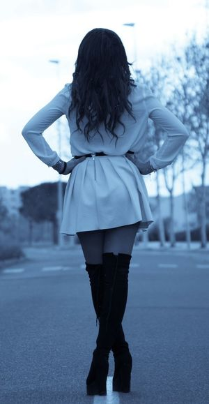Rear view of fashionable young woman standing on road