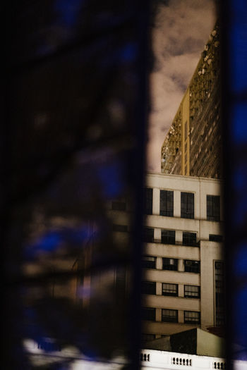 Reflection of building on glass window at night
