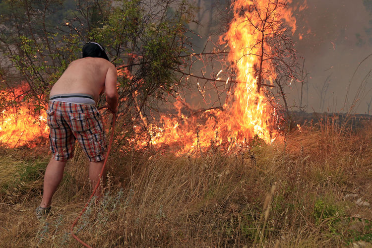Rear view of man standing by bonfire on field