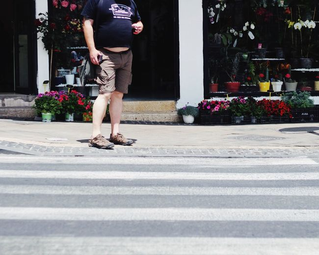 Low section of man standing on sidewalk against flower shop during sunny day