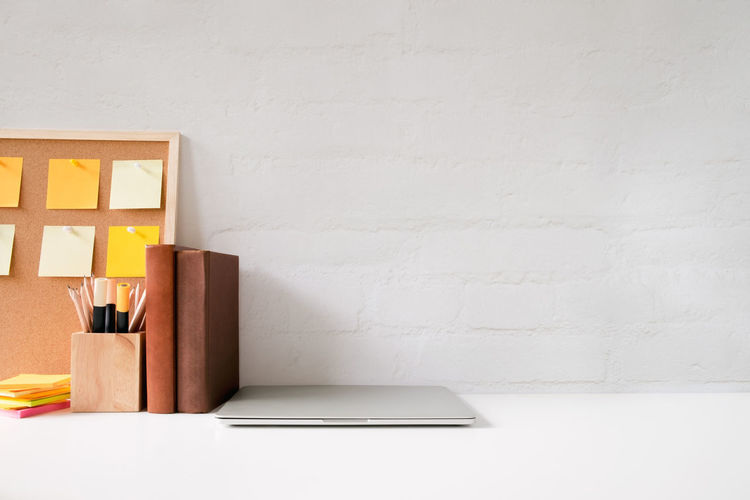 Close-up of laptop with book on table against white wall