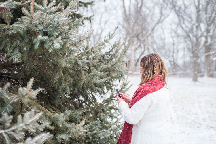 Woman walking on snow covered tree