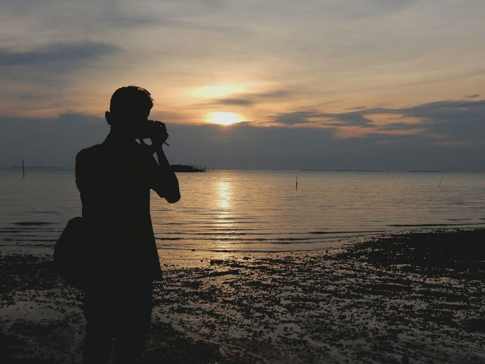 Rear View Of Silhouette Man Photographing While Standing On Shore During Sunset