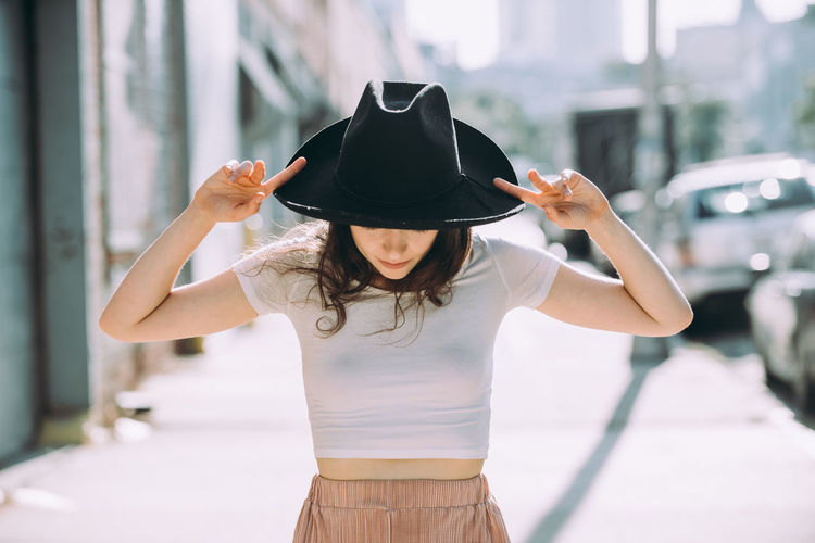 Midsection of woman holding hat while standing outdoors