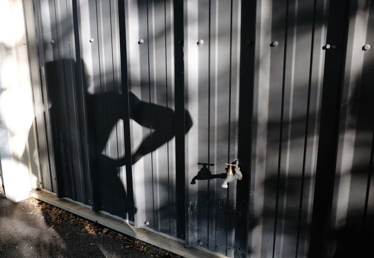 Tap on metallic fence with shadow of person