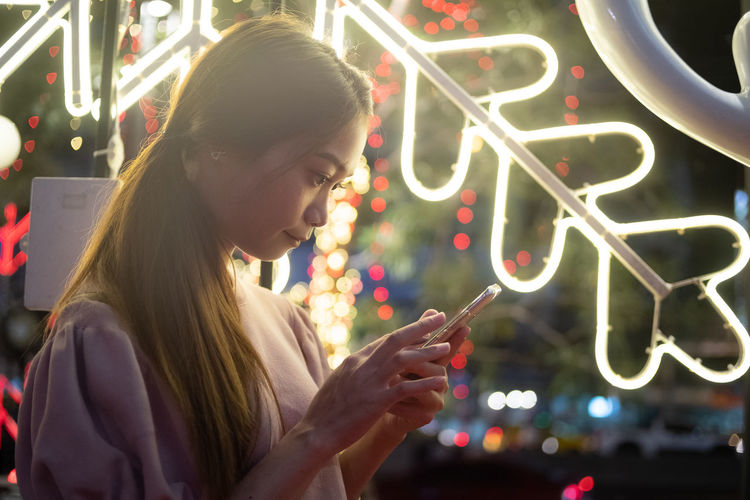 Full length of young woman using mobile phone at night