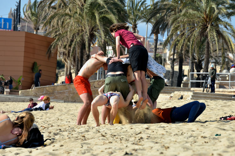 group of young girls and guys enjoy and relax in Palma de Mallorca beach Real People Group Of People Leisure Activity Full Length Outdoors Sand Beach Guys And Girls Enjoying Life Playing Nature People Adult Casual Clothing Day Palma De Mallorca FreeTime Lifestyles Togetherness Friendship