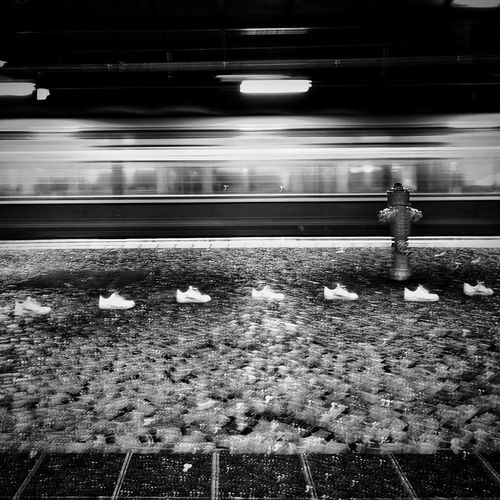 Rear view of person standing at railroad station at night