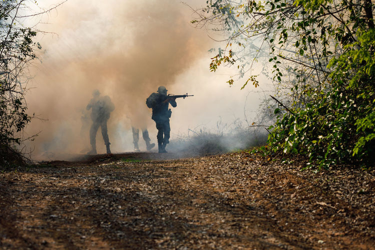 Gun Teamwork Day Fog Forest Full Length Government Land Men Nature Outdoors People Plant Real People Rear View Smoke - Physical Structure Soldiers Uniform Standing Tree Uniform War