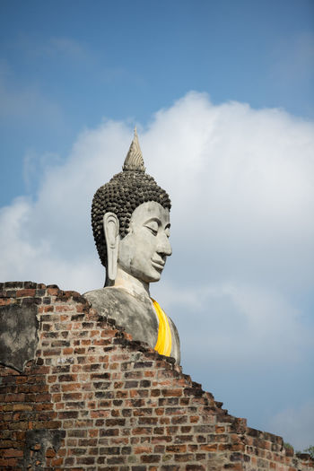 Low angle view of brick wall and buddha statue against cloudy sky