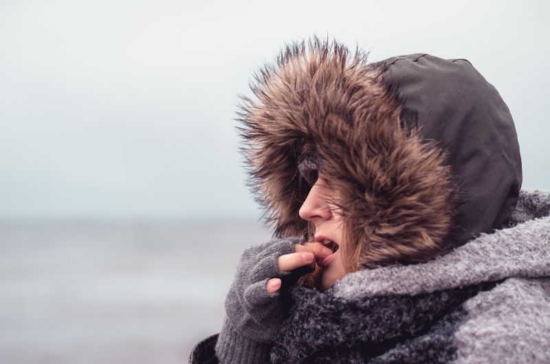Close-up of woman wearing warm clothing against sky