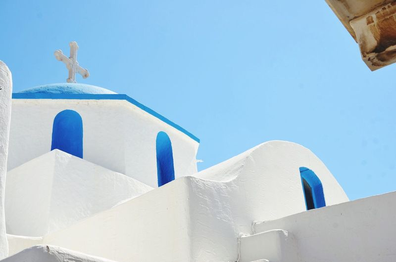 Low angle view of white church in santorini against clear sky
