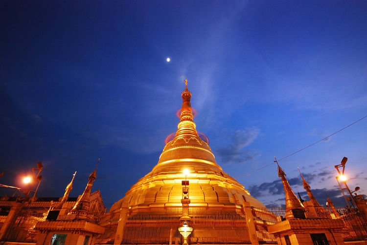 Low angle view of illuminated temple against blue sky