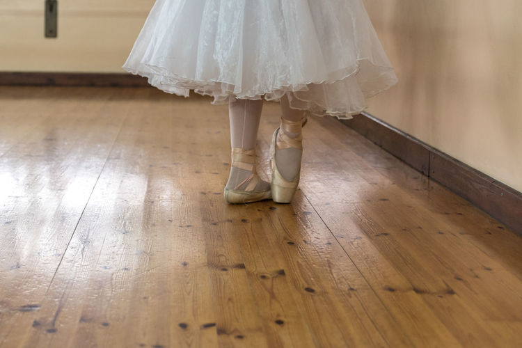 Low Section Of Ballet Dancer On Hardwood Floor