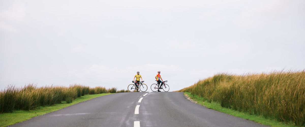 Two cyclist stops in the middle of a road near Bowland Forest CyclingUnites Lancashire Relaxing Roadbike Adventure Cycling Full Length Grass Headwear Landscape Leisure Activity Nature Outdoors People Road Rural Scene The Way Forward Togetherness Two People