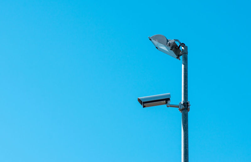 Low angle view of security system on street light against blue sky