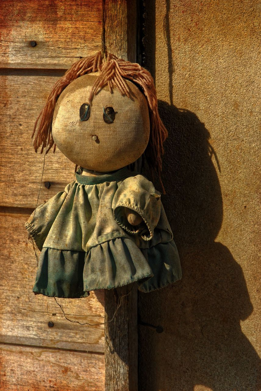 Old Doll Hanging On Wooden Door Against Wall