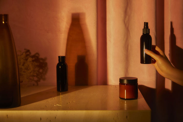 Midsection of wine bottles on table against wall