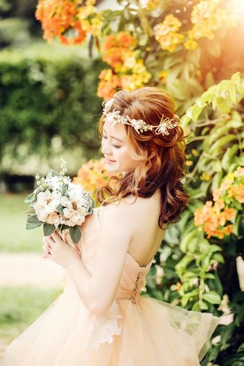 Side view of beautiful bride holding bouquet while standing by plants at park