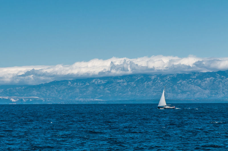 Sailboat Sailing In Sea Against Blue Sky