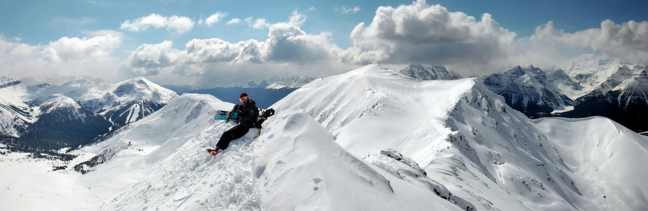 Person Sitting On Snow Heap Against Sky