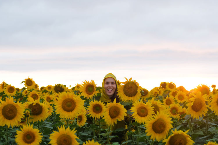 Portrait of happy woman tourist in yellow raincoat standing in sunflower field in summer evening.
