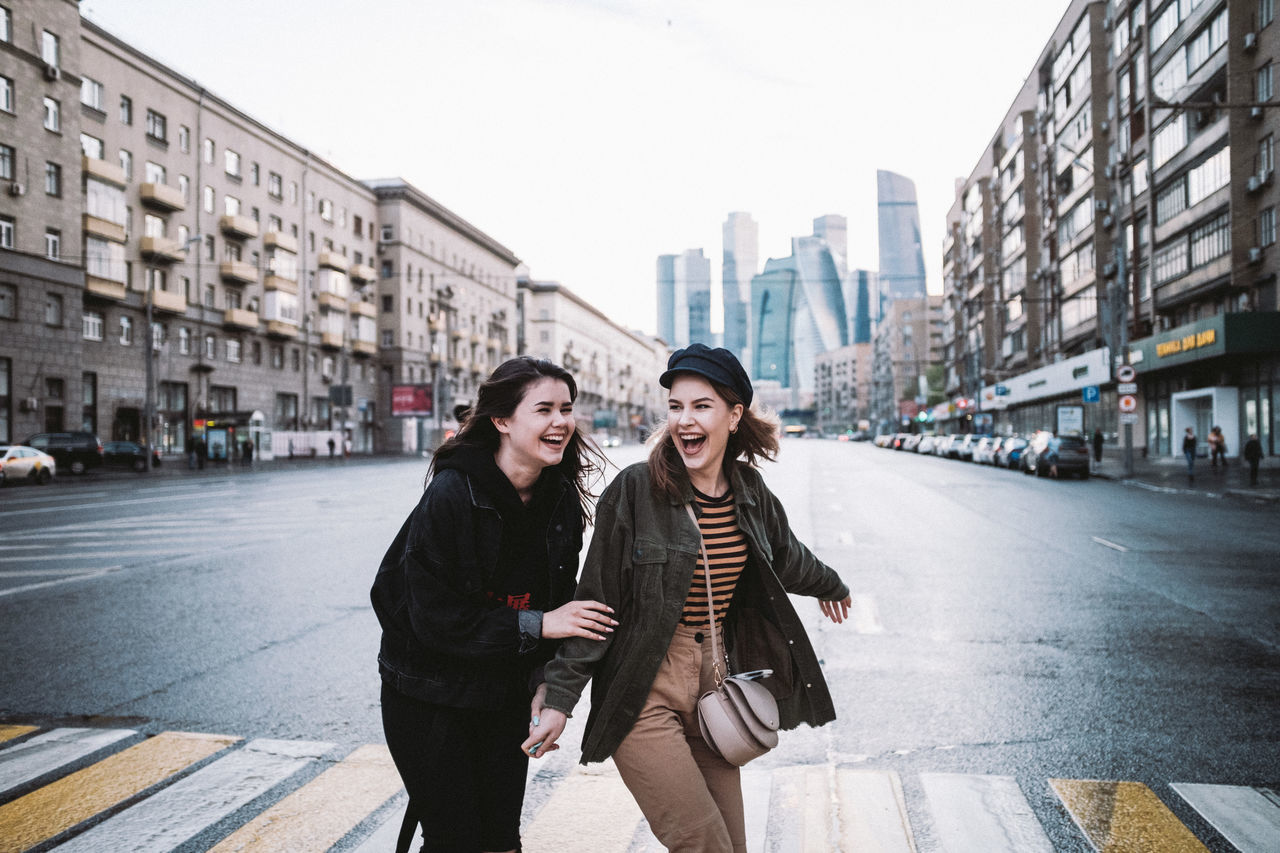 Happy friends on road in city