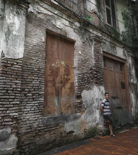 Full length of man standing against old building