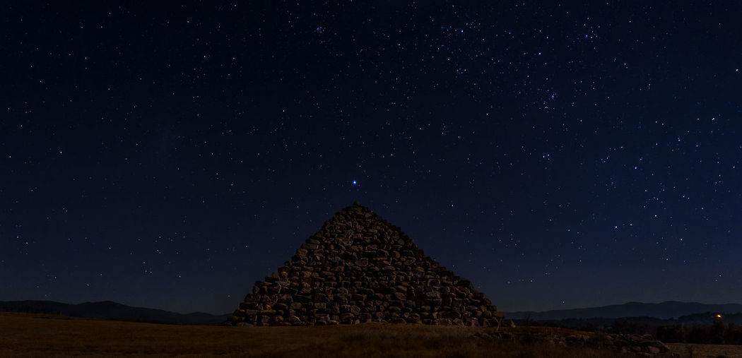 Mountain against star field sky at night