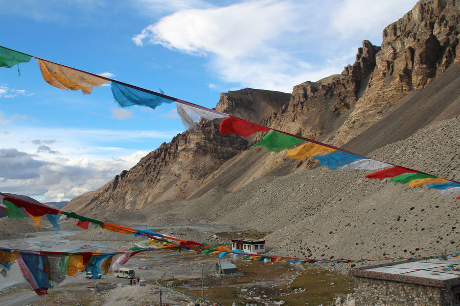 View of mountains with the sutra streamers, bus and tourist at Everest Base Camp, Tibet. Cloud - Sky Colourful Day Everest Base Camp Flag Landscape Mountain Mountain Range Multi Colored No People Outdoors Sky Tibetan Prayer Flags