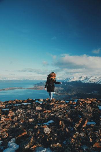 Woman standing on rocks against sky