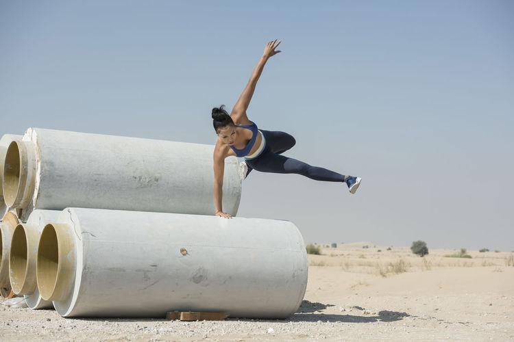 Black African American athletic woman jumps over and leaps from construction pipes wearing sports outfit in a parkour or extreme fitness competition. Athlete Athletics Black Woman Parkour And Free Running African American Woman Construction Pipes Day Desert Landscape Fitness Training Full Length Jumping Leaping One Person Outdoors People Real People Skills  Sky Young Adult Young Women Fresh On Market 2018