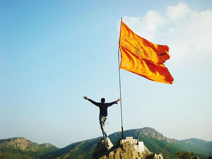 Rear view of man with arms outstretched while standing on rocky mountain with flag
