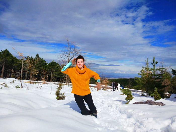 Portrait of smiling woman falling on snowy field