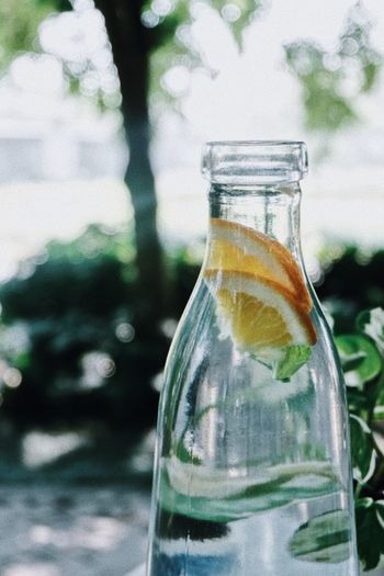 Close-up of lemon slices and drink in glass jar outdoors