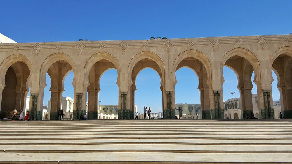 Hassan II Mosque Mosque Hassan Arch Architecture Built Structure Blue Clear Sky Building Exterior Architectural Column Steps Tourism Column Famous Place Low Angle View Travel Destinations Group Of People Façade Pillar Colonnade Arcade Arched Day Casablanca, Morocco Morocco